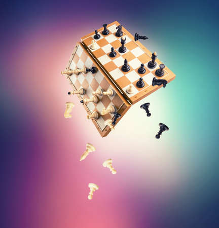 chessmen: Chessmen falling from the chessboard over colorful background Stock Photo