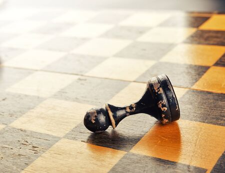 Old black pawn lying on the chess board