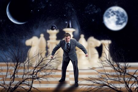 pawn adult: Businessman in front of the white team on chess board against night sky