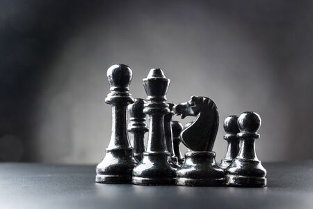 Set of black chess figures on the table over black Stock Photo