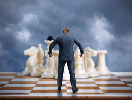 pawn adult: Businessman on the chess board ready to fight with white chess team Stock Photo