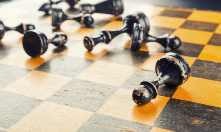 defeated: Old wood chess figures lying on the board defeated