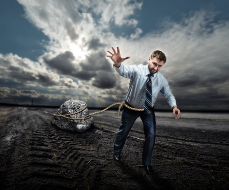 oppressed: Businessman pulling a big stone on the ground