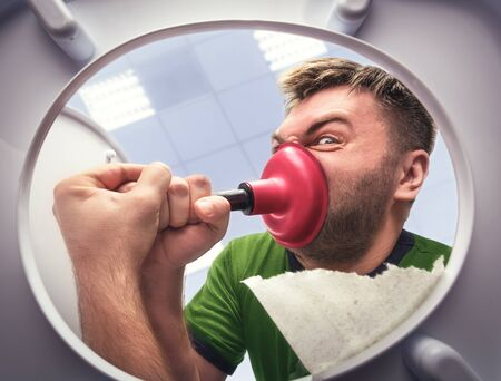 unblock: Man cleaning the toilet with cup plunger