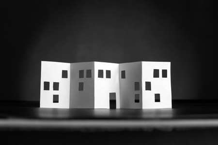 windows and doors: White paper building with cut windows and doors over black