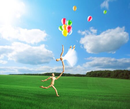 flying woman: Wedding couple of wooden carved figures, man holging by hand flying woman with ballons Stock Photo