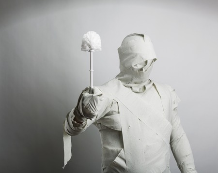 toilet brush: Man covered with toilet paper playing with toilet brush Stock Photo