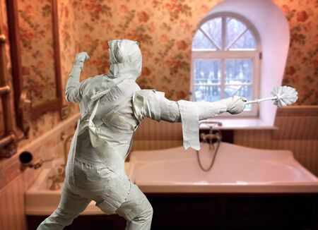 toilet brush: Man covered with toilet paper playing with toilet brush in the bathroom