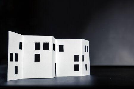 silhouette maison: Blanc bâtiment de papier avec des fenêtres découpées sur noir