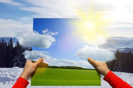snow field: Male hands holding picture with summer landscape over winter nature Stock Photo