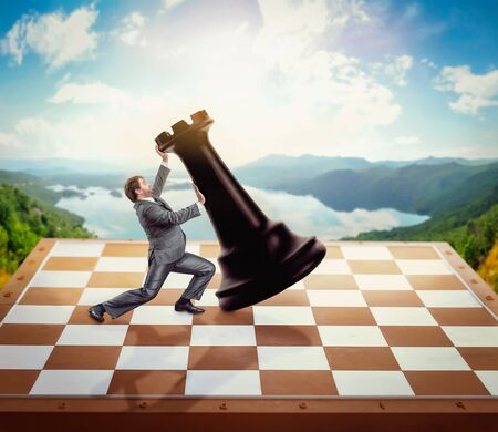 chessman: Businessman fighting with a chessman on chess board over nature background