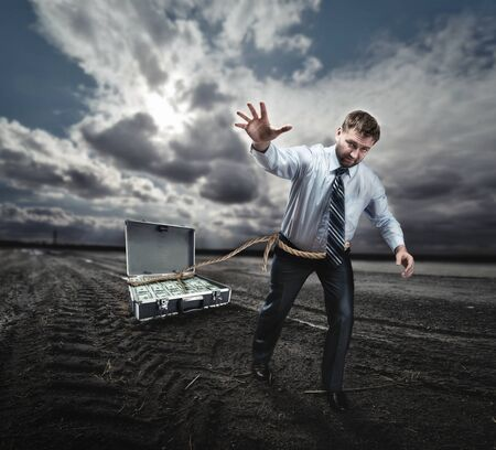 pulling money: Businessman with rope round his waist pulling suitcase full of money