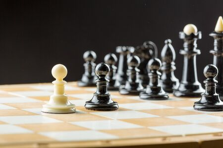 White pawn standing in front of the black chess team Stock Photo