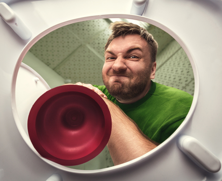 Man cleaning the toilet with cup plunger
