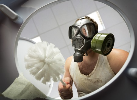 toilet brush: Man in gas mask with brush cleaning the toilet bowl