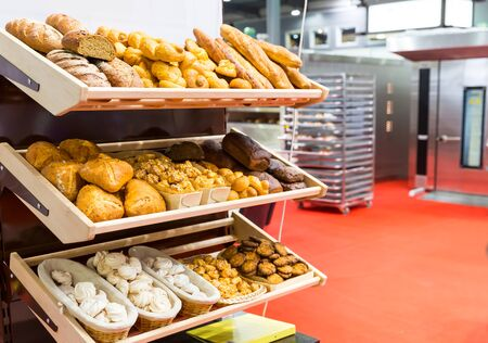 bakery store: Loaves of bread and fresh buns on the shelves in the bakery kitchen Stock Photo