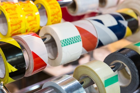 Rolls of different packing scotch tapes in the shop close up