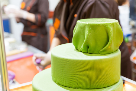 gumpaste: Tasty cake with gum paste and baker on the background