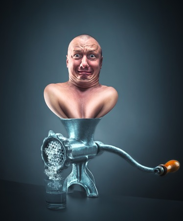 mincing: Retro mincing machine with scared man inside Stock Photo