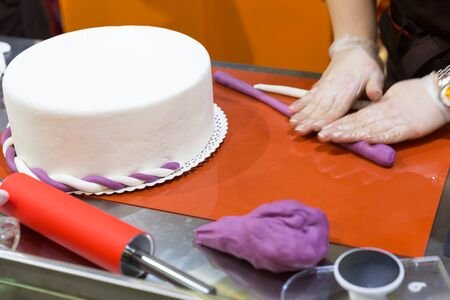 gum paste: Baker hands decorating cake with gum paste Stock Photo