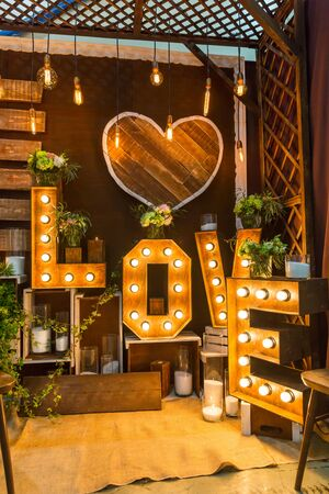 lamp light: Romantic room with garland with lights and wooden letters of love Stock Photo
