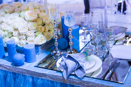 blue candles: Wedding decorated restaurant with bouquets and blue candles