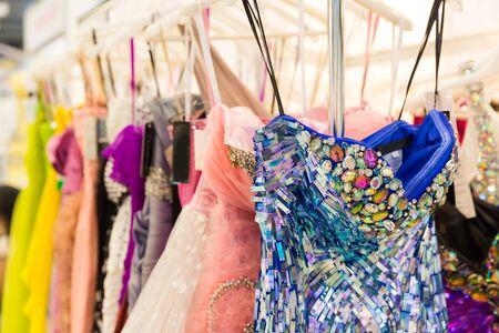 anochecer: Conjunto de vestidos de moda en la madera perchas en la tienda Foto de archivo