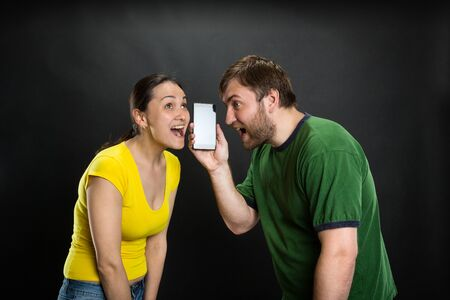 anecdote: Young couple listening to joke using smartphone over black background
