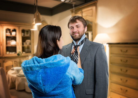 young wife: Young wife tieing a tie to her smiling husband Stock Photo