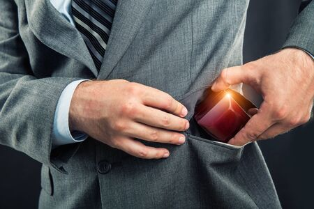 giftbox: Businessman putting a gift-box in the pocket close up