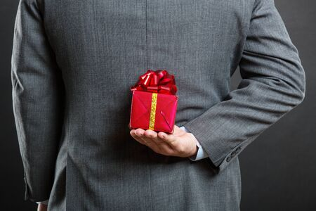 gift behind back: Businessman hiding a gift behind his back