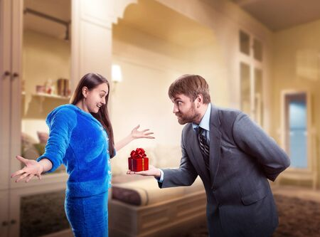 gift behind back: Businessman giving a gift to his wife, woman is surprised