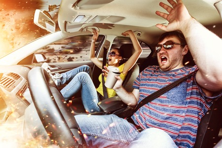 Scared couple with beverages in the burning car Stock Photo