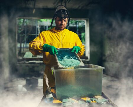 protective suit: Man in protective outerwear suit sorts crystal meth in little packs