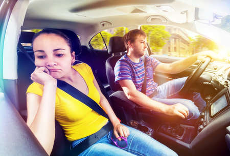 bored woman: Man driving the car, bored woman sitting next to him Stock Photo