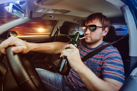 drinking and driving: Man driving the car, drinking wine and smoking