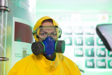 toxic: Woman wearing protective outerwear suit in chemical laboratory with flask