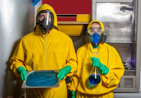 protective: Man and woman in protective suits cooking meth in the lab