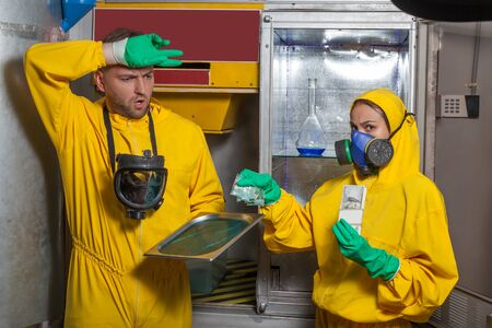 methamphetamine: Man and woman in protective suits cooking meth in the lab