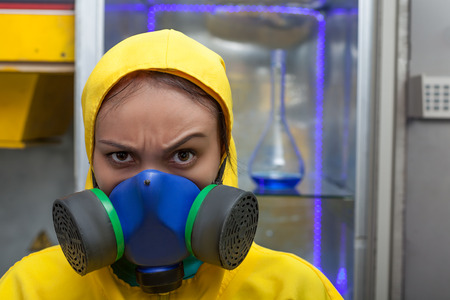 protective suit: Woman wearing protective outerwear suit in chemical laboratory with flask