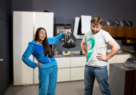 아내가 부엌에서 쓰레기를 꺼내달라고 남편에게 요구했습니다. 스톡 콘텐츠