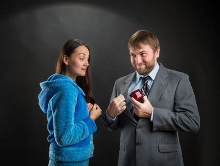 interested: Businessman putting out a ring-box, woman is interested in it Stock Photo