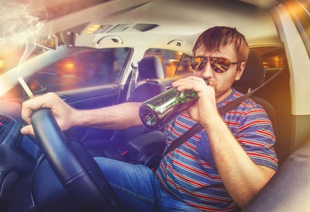 drinking driving: Man driving the car, drinking wine