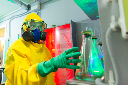 protective suit: Woman wearing protective outerwear suit works in chemical laboratory