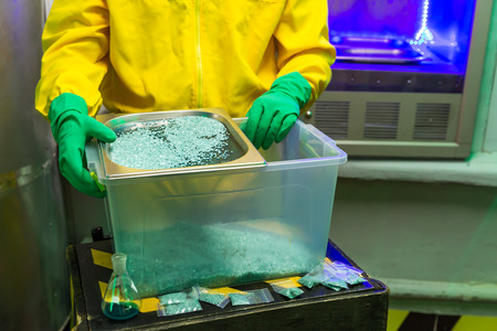 meth: Man in protective outerwear suit sorts crystal meth in packs