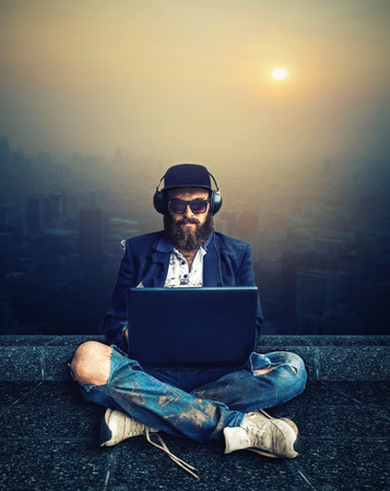 poorness: Cool vagrant sitting in earphones with computer on the roof