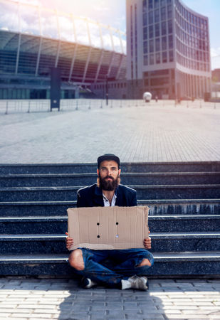 joblessness: Homeless sitting with pieces of cardboard at the steps Stock Photo