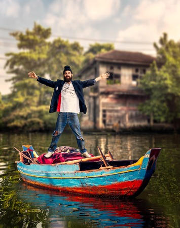 undeveloped: Vagrant standing on the boat over dirty canal with slums