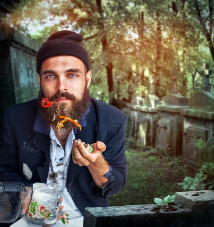 joblessness: Desperate vagrant with food on his beard eating Stock Photo