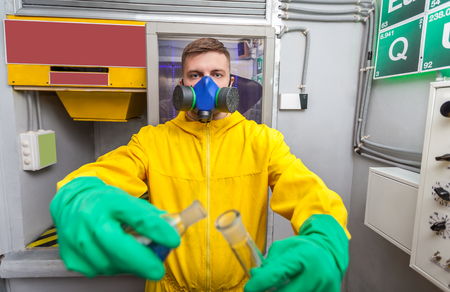 protective: Man in protective suit working with tubes while cooking meth